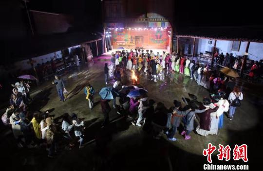 摩梭小伙和摩梭姑娘与游客们手拉着手跳舞。王磊 摄
